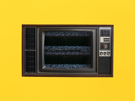 Old vintage televisions that can't receive signals on yellow background.