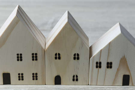 Front of the wooden model house on wooden background.