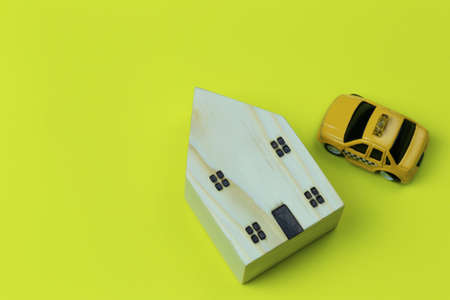 Wooden model house and toy car on yellow paper background and have copy space.
