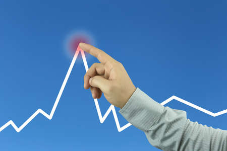 Business men's hand pointing to the top of graph in concept of profits in the business.