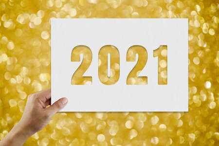 Hand of man holding 2021 text on gold bokeh background for design in your work Christmas and New Year.