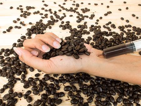 caffeine: coffee beans and hand syringe , mean to addiction caffeine Stock Photo