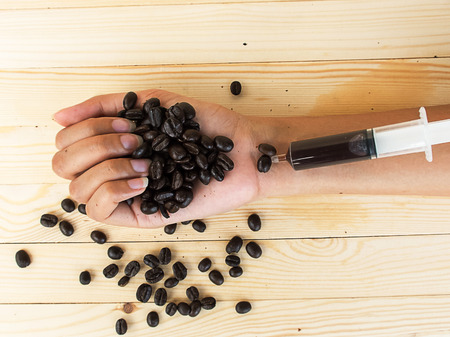 caffeine: coffee beans and hand syringe , mean to caffeine addiction
