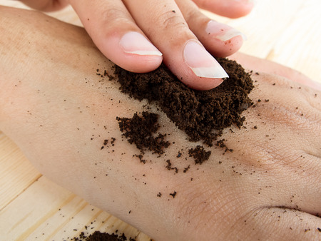 hand rubbing: close up coffee hand scrub with ground coffee dry  , mean to beauty or cosmetic Stock Photo