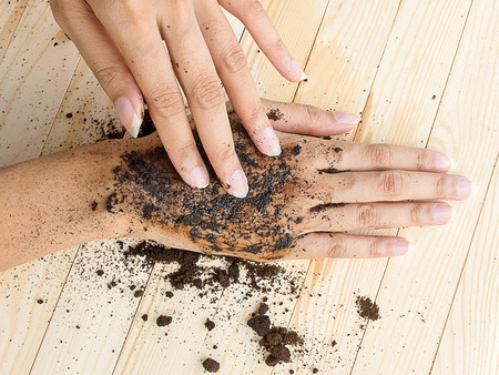 hand rubbing: coffee hand scrub with ground coffee wet  , mean to beauty or cosmetic