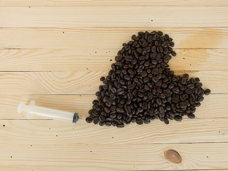 caffeine: coffee beans and syringe, mean to caffeine addiction