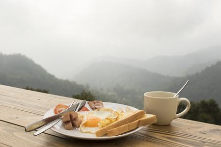 colazione: prima colazione e tazza di caffè sul tavolo in legno con sfondo la natura montagna