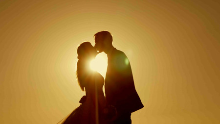 Silhouette kissing at sunset bride and groom Stockfoto