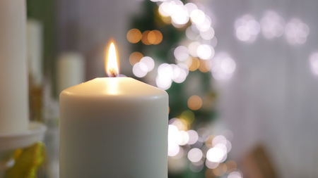 Christmas candles and ornaments on a dark background with lights