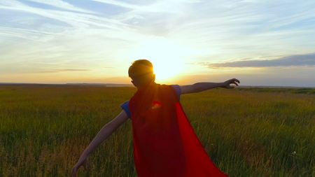 Boy dressed with a superhero cape running in a field, looking into the sunset Stockfoto