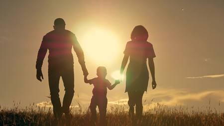 Happy young family with children running around the field
