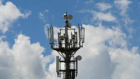 telecommunication cellular tower against blue sky, with room for copy space
