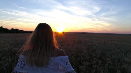 Romantisch meisje in een witte kleding die op de gouden tarwegebieden loopt in de zon Stockfoto - 88281562