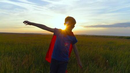 Een jongen in een superkostuum loopt over het groene veld bij zonsondergang Stockfoto - 88617026