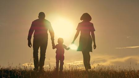 Happy young family with children running around the field, silhouette at sunset