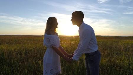 Young beautiful couple in a wheat field. Silhouette on sunset background. Slow motion Stockfoto