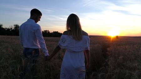 Jong mooi paar op een tarwegebied. Silhouet op zonsondergang achtergrond. Slow motion Stockfoto - 88931001