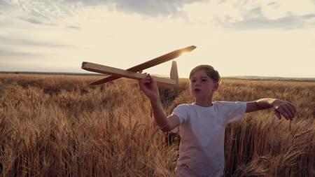 Gelukkige kindlooppas met een stuk speelgoed vliegtuig op een zonsondergangachtergrond over een tarwegebied Stockfoto - 88931002