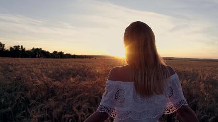 Romantisch meisje in een witte kleding die op de gouden tarwegebieden loopt in de zon Stockfoto - 88931004