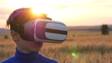 A boy stands in a wheat field at sunset in virtual glasses