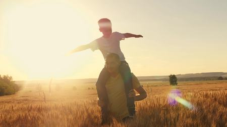 The father wears his son on his shoulders A walk on the wheat field during sunset. Family game