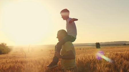 De vader draagt ??zijn zoon op zijn schouders Een wandeling op het korenveld tijdens zonsondergang. Familiespel Stockfoto - 88931107
