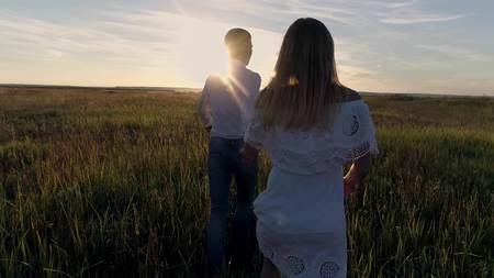Jong koppel jongen en meisje loopt over het veld naar de zonsondergang Stockfoto - 88931103