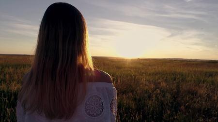 Romantisch meisje in een witte kleding die op de gouden tarwegebieden loopt in de zon Stockfoto - 88931110