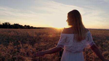 Romantisch meisje in een witte kleding die op de gouden tarwegebieden loopt in de zon Stockfoto - 88931189
