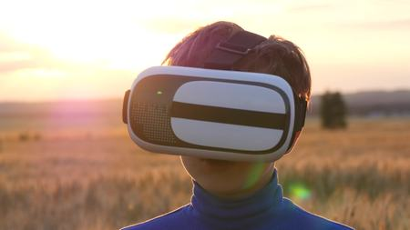 A boy stands in a wheat field at sunset in virtual glasses. Playing outdoors on a sunny day