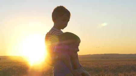Twee jongens die bij zonsondergang op een tarwegebied onder gouden aartjes spelen Stockfoto - 89039396