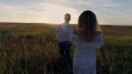 Jong koppel jongen en meisje loopt over het veld naar de zonsondergang Stockfoto - 89039397