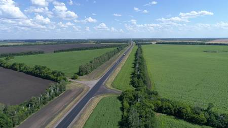 Aerial shot of transport traffic on the road in the countryside. Highway in the woods near the villages, Russia