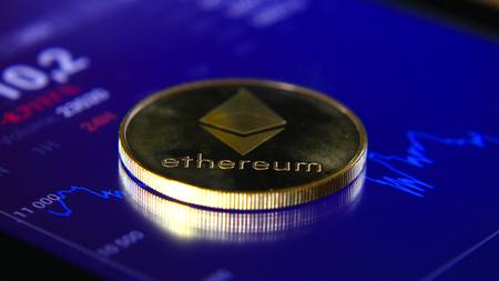 Gold coins of the ethereum on the background of a graphic stock chart. The Concentration of the Crypto-Currency of Virtual Money