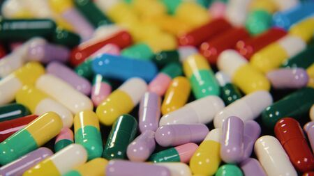 Pharmaceutical drug, a bunch of multi-colored round capsules of tablets with antibiotic medicine in packages. Disease treatment concept