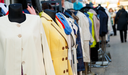 togs: Row of mannequins with different coloured womens clothes on market. Some outwear examples in a line before shop. Clothes sale concept.