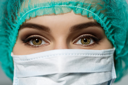 surgeon mask: Female doctors face wearing protective mask and green surgeons cap closeup. Surgeons eyes close up gazing intently in camera. Resuscitation concept. Stock Photo