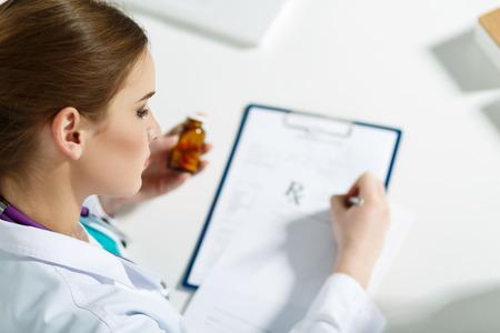 farmacia: Hermosa joven médico sentado frente a la mesa de trabajo, sosteniendo recipiente con pastillas y Prescripción de la escritura. Concepto médico o farmacia. Doctor de sexo femenino hermoso que hace el papeleo con la concentración