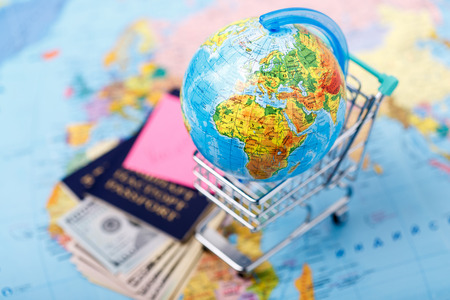 Passports, money, tickets, globe and map of the world as a vacation concept. Summer journey preparation. Planning holidays, cheking documents, choosing destination point, having fun. Stock Photo