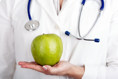 phonendoscope: Female doctors hand holding green fresh apple. Medical help or insurance concept. Health life and wholesome food concept.