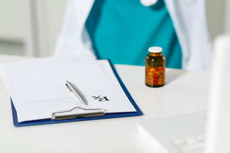 doctor writing: Medical doctor siting in front of working table and writing prescription. Medical and pharmacy concept. Jar of pills on table with prescription.