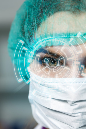futuristic effect: Female doctors face wearing protective mask and green surgeons cap closeup. Surgeons eyes close up gazing intently in camera with futuristic effect. Resuscitation concept.