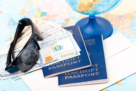 vacation destination: Passports money tickets globe and map of the world as a vacation concept. Summer journey preparation. Planning holidays cheking documents choosing destination point having fun.
