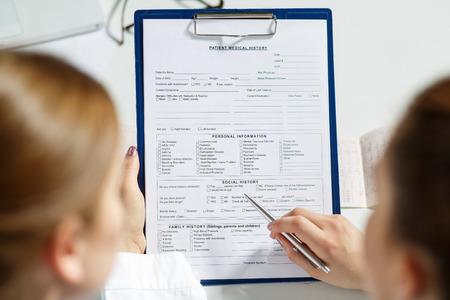 Dos mujeres médicos que examinan la lista de la historia clínica del paciente. Conversación profesional, el consejo de los médicos. Conferencia de trabajo.