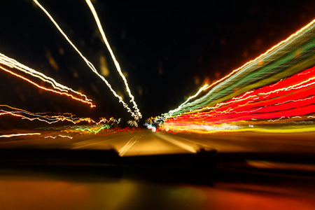 Drunken driving concept. Speedy night driving. Sleepy driver looking on night road. Drugs and alcohol effect. Blurry and blending road during high speed trip. Stock Photo