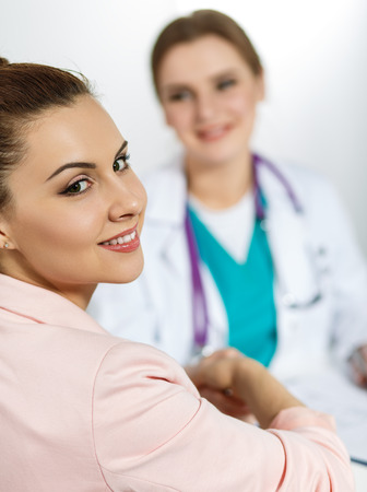 handclasp: Beautiful female patient shaking hands with doctor. Partnership trust and medical ethics concept. Handshake with satisfied client. Thankful handclasp for excellent treatment.