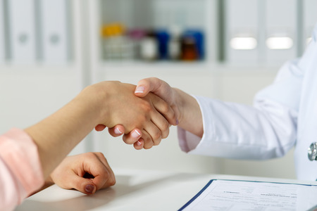 handclasp: Female doctor shaking hands with patient. Partnership trust and medical ethics concept. Handshake with satisfied client. Thankful handclasp for excellent treatment.