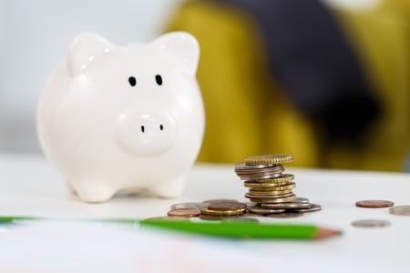 テーブルのクローズ アップに白い piggybank 近く異なる硬貨の山。予算作成の費用概念。貯蓄をし、効果的な投資の概念