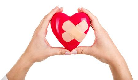 reanimować: Kobieta ręce podniesione gospodarstwa czerwone serce naprawione zabawki na białym tle. Pomoc medyczna i ubezpieczenia koncepcji. Opieka Kardiologia i zdrowie. Operacji serca i resuscytacja koncepcja