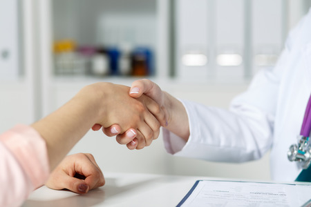 business deal: Female doctor shaking hands with patient. Partnership, trust and medical ethics concept. Handshake with satisfied client. Thankful handclasp for excellent treatment. Stock Photo